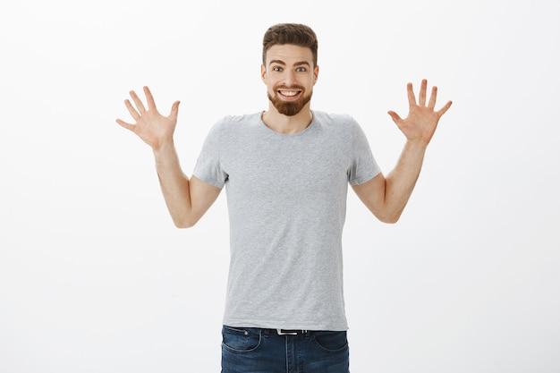 Portret van opgewonden en opgewonden gelukkig knappe volwassen man met baard, snor en blauwe ogen die de handpalmen opheft met tien vingers en breed lacht terwijl hij verbaasd geweldig nieuws vertelt tegen een grijze muur
