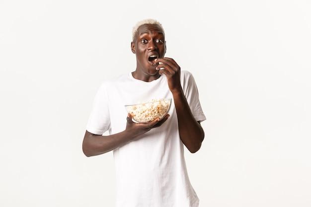 Portret van opgewonden en verbaasd afro-amerikaanse jongeman genieten van kijken naar film of tv-serie, popcorn eten met opgewonden uitdrukking