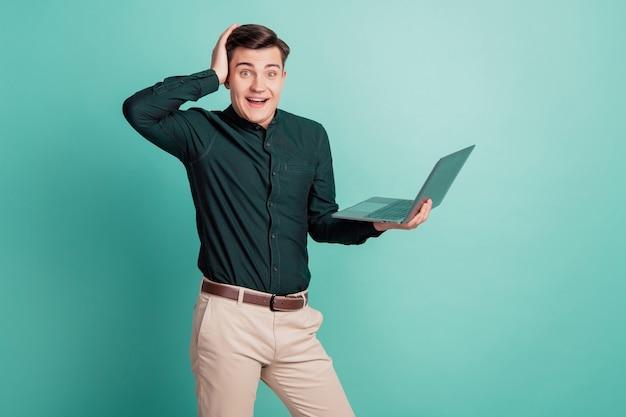 Portret van opgewonden funky programmeur man houdt laptop hand hoofd verbaasde reactie op groenblauw achtergrond