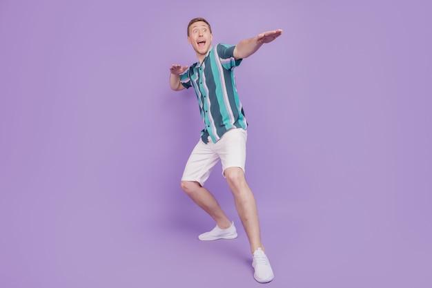 Portret van opgewonden gekke geschokte verbaasde man dans kijkt lege ruimte open mond op violette achtergrond
