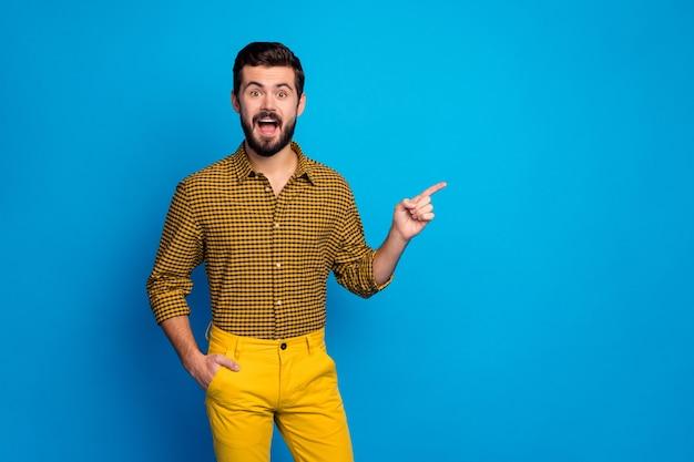 Portret van opgewonden gekke man promotor demonstreren ongelooflijke advertenties promo onder de indruk schreeuw wow omg punt wijsvinger copyspace slijtage geruite broek glans geïsoleerd over blauwe kleur