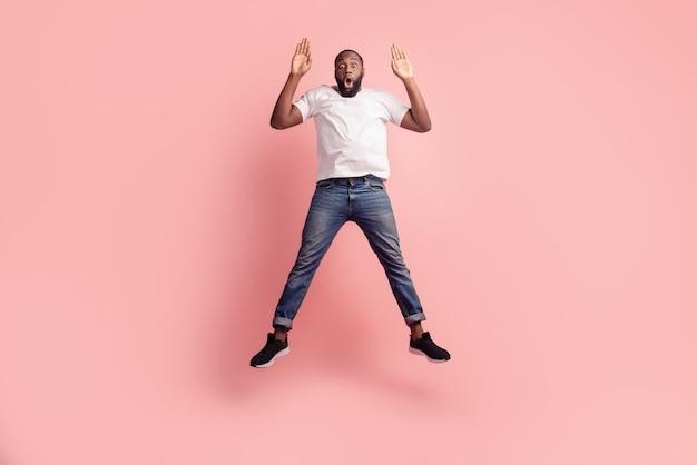 Portret van opgewonden gekke onzorgvuldige man springen op roze achtergrond