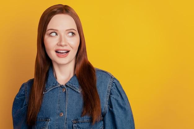 Portret van opgewonden gekke schattige dame kijkt lege ruimte open mond op gele achtergrond