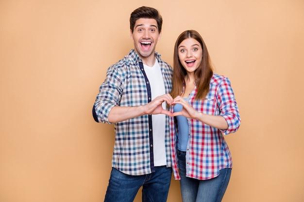Portret van opgewonden gekke twee mensen getrouwd stel vingers hartsymbool van aanhankelijk romantische liefde dragen casual stijl kleding geïsoleerd op beige kleur achtergrond