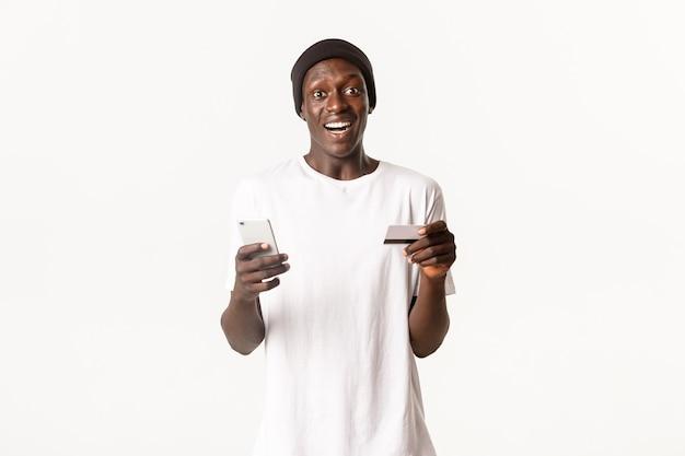 Portret van opgewonden, gelukkige afro-amerikaanse jonge mannelijke student, met creditcard en smartphone met geamuseerde glimlach