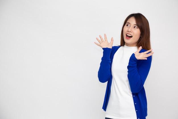 Portret van opgewonden gillende jonge aziatische vrouw die over witte muur wordt geïsoleerd.
