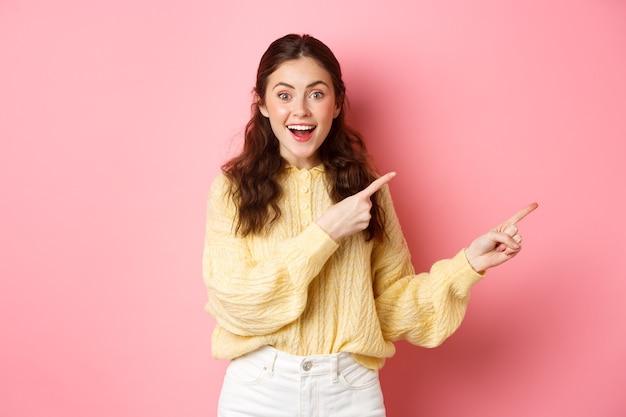 Portret van opgewonden glimlachende vrouw die informatie geeft, de weg wijst, de vingers recht op copyspace opzij richt, opgewekt tegen de roze muur staand.