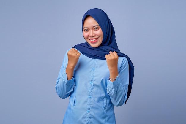 Portret van opgewonden jonge aziatische vrouw die hijab draagt met geluksuitdrukking