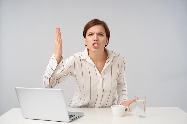 Portret van opgewonden jonge bruinharige vrouw met natuurlijke make-up emotioneel hand opheffen en haar tanden tonen terwijl ze fel kijkt, zittend aan tafel op wit