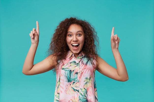 Portret van opgewonden jonge bruinogige krullende brunette dame die verbaasd kijkt met opgetrokken wenkbrauwen en naar boven wijst met wijsvingers, geïsoleerd op blauw
