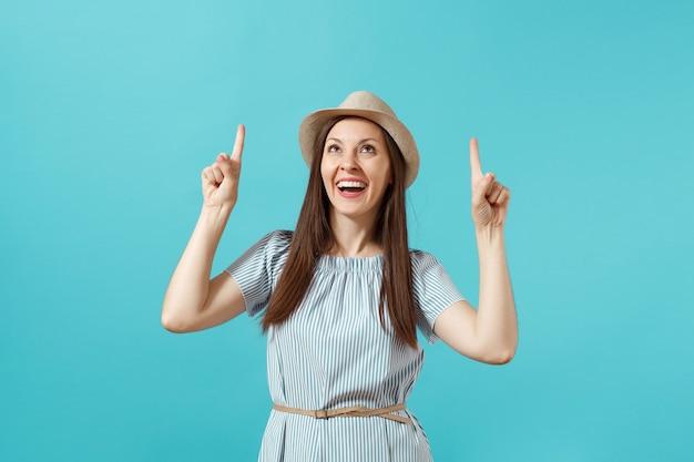 Portret van opgewonden jonge elegante vrouw gekleed in jurk, stro zomerhoed wijzende wijsvingers omhoog op kopieerruimte geïsoleerd op blauwe achtergrond. mensen oprechte emoties levensstijl concept. advertentiegebied