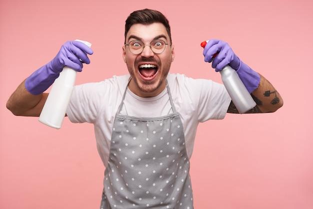 Portret van opgewonden jonge korte brunette man met tatoeages emotioneel verhogen zijn handen met spuitflessen met brede mond geopend, poseren op roze