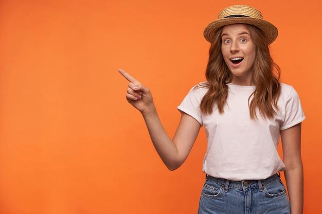 Portret van opgewonden jonge krullende vrouw met rood haar die met wijd geopende ogen kijkt, opzij toont met wijsvinger, vrijetijdskleding draagt