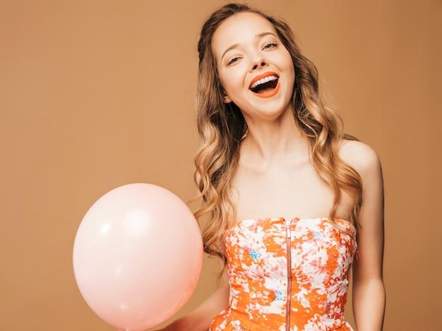 Portret van opgewonden jonge meisje poseren in trendy zomer kleurrijke jurk. glimlachende vrouw met het roze ballon stellen. model klaar voor feest