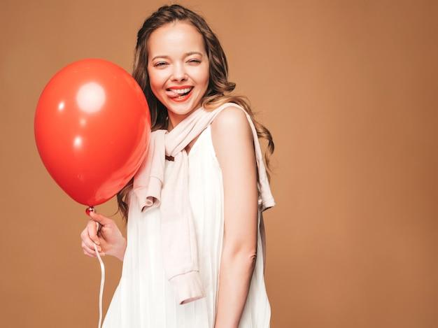 Portret van opgewonden jonge meisje poseren in trendy zomer witte jurk. glimlachende vrouw met het rode ballon stellen. model klaar voor feest