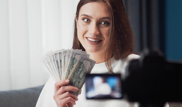 Portret van opgewonden jonge schoonheid die vlog fotografeert die camera bekijkt en waaiervormige dollars toont