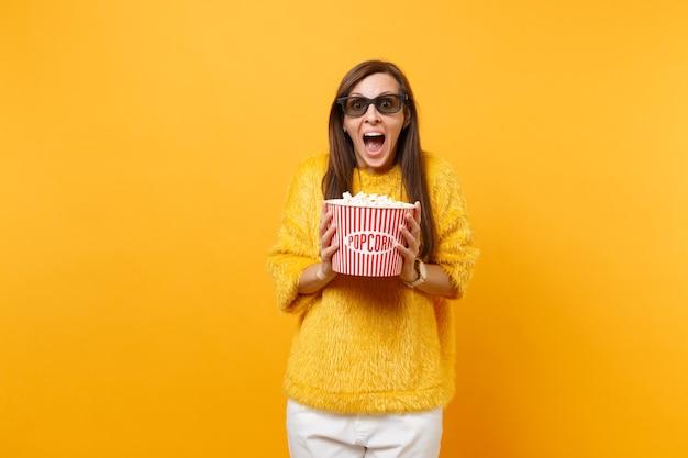 Portret van opgewonden jonge vrouw in 3d-imax-bril die filmfilm kijkt, schreeuwt, emmer popcorn vasthoudt die op felgele achtergrond wordt geïsoleerd. mensen oprechte emoties in de bioscoop, lifestyle concept.