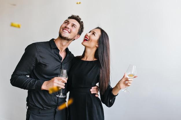 Portret van opgewonden jonge vrouw omarmen met echtgenoot op evenement en poseren met confetti