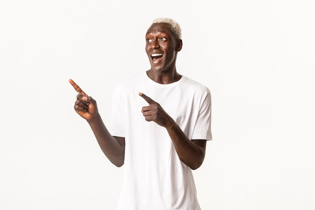 Portret van opgewonden knappe afro-amerikaanse blonde kerel, die blij en verbaasd kijkt naar het logo, de linkerbovenhoek met de vingers wijzend