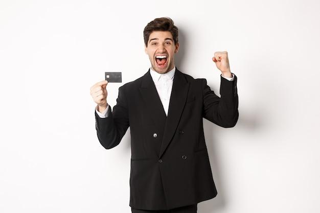 Portret van opgewonden knappe zakenman in pak, vreugde en creditcard tonen, staande tegen een witte achtergrond.