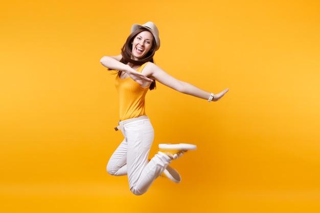 Portret van opgewonden lachende jonge gelukkig springende hoge vrouw in stro zomerhoed, kopieer ruimte geïsoleerd op geeloranje achtergrond. mensen oprechte emoties, passie levensstijl concept. reclame gebied.