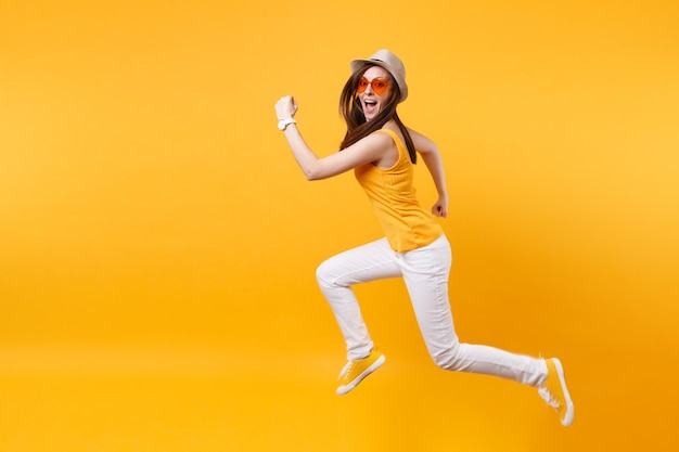 Portret van opgewonden lachende jonge springende hoge vrouw in stro zomer hoed, oranje bril kopieer ruimte geïsoleerd op gele achtergrond. mensen oprechte emoties, passie levensstijl concept. reclame gebied.