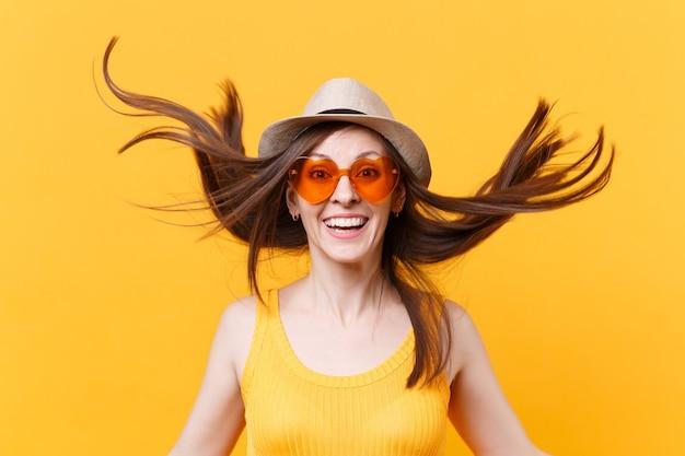 Portret van opgewonden lachende jonge vrouw in stro zomer hoed, oranje bril met fladderende haar kopie ruimte geïsoleerd op gele achtergrond. mensen oprechte emoties, lifestyle concept. reclame gebied.