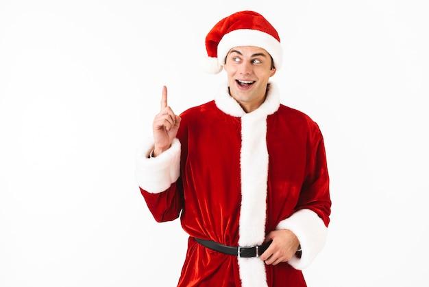 Portret van opgewonden man 30s in kerstman kostuum en rode hoed gebaren vinger omhoog