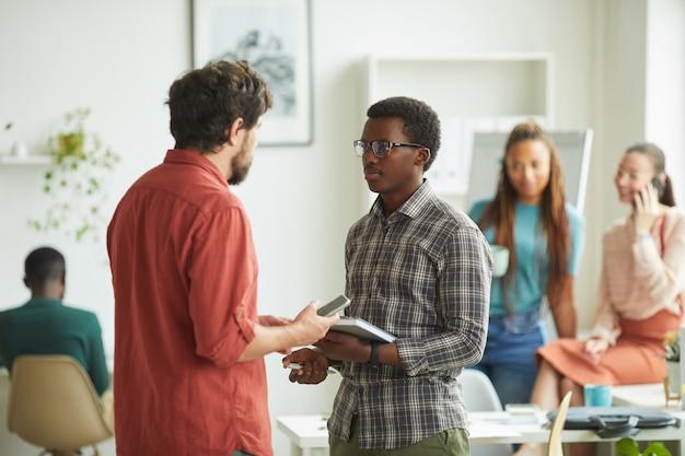 Portret van opgewonden manager die jonge afrikaans-amerikaanse man instrueert terwijl hij in bureau staat