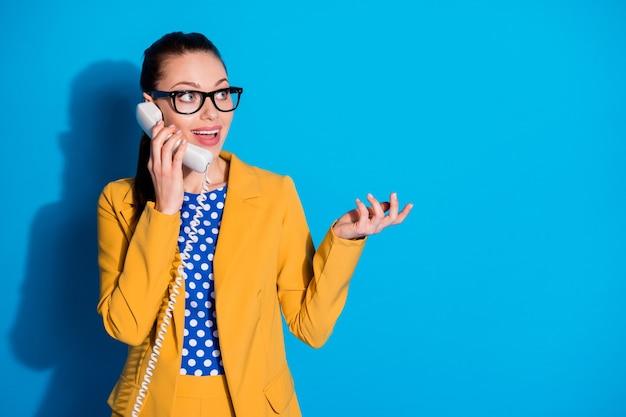 Portret van opgewonden marketeer bankier assistent meisje oproep telefoon vriend vertellen praten zeggen spreken zakelijk nieuws dragen gele gestippelde blazer jas geïsoleerd over blauwe kleur achtergrond