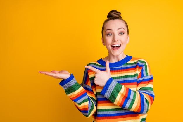Portret van opgewonden meisje promotor geeft ongelooflijke advertentie promotie houd hand punt wijsvinger copyspace draag trui geïsoleerd over glans kleur achtergrond