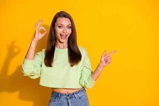 Portret van opgewonden meisje wijs wijsvinger copyspace toon ok sig