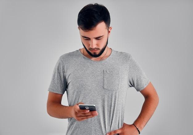 Portret van opgewonden met behulp van smartphone voor het verzenden van sms geïsoleerd op een grijze achtergrond kopie-sapce