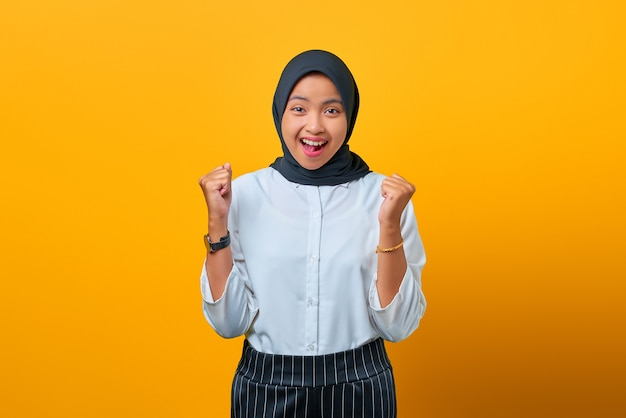 Portret van opgewonden mooie aziatische vrouw die succes viert op gele achtergrond