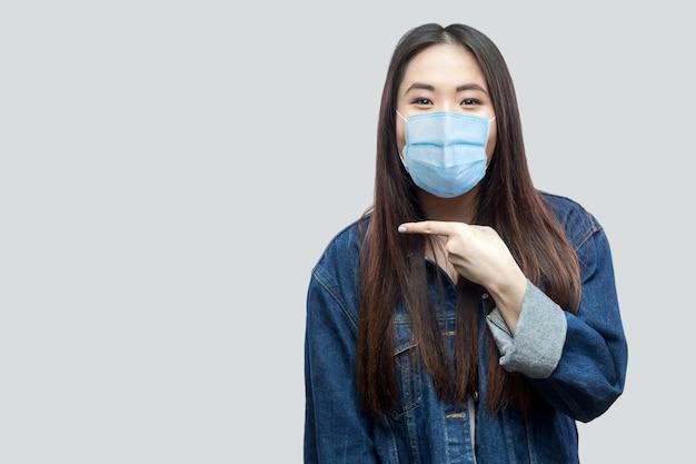 Portret van opgewonden mooie brunette aziatische jonge vrouw met medisch masker in casual blauw spijkerjasje dat staat en wijst op copyspace met een verbaasd gezicht. studio opname, geïsoleerd op een grijze achtergrond.
