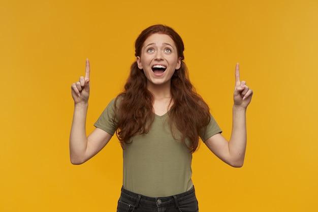 Portret van opgewonden, mooie dame met lang gemberhaar. groen t-shirt dragen. mensen en emotie concept. kijkend naar en wijzende vingers op kopie ruimte, geïsoleerd over oranje muur