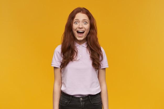 Portret van opgewonden, mooie dame met lang gemberhaar. roze t-shirt dragen. mensen en emotie concept. ik ben verbaasd je te zien. geïsoleerd over oranje muur