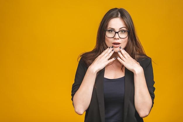 Portret van opgewonden mooie zakenvrouw in glazen en jas staat op een gele muur, verrast.