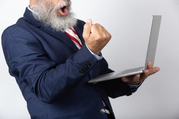Portret van opgewonden oudere man gekleed pak met behulp van een laptop en het vieren van succes geïsoleerd op een witte achtergrond.