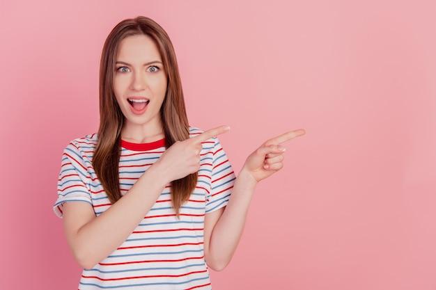 Portret van opgewonden promotor dame directe wijsvingers lege ruimte op roze achtergrond