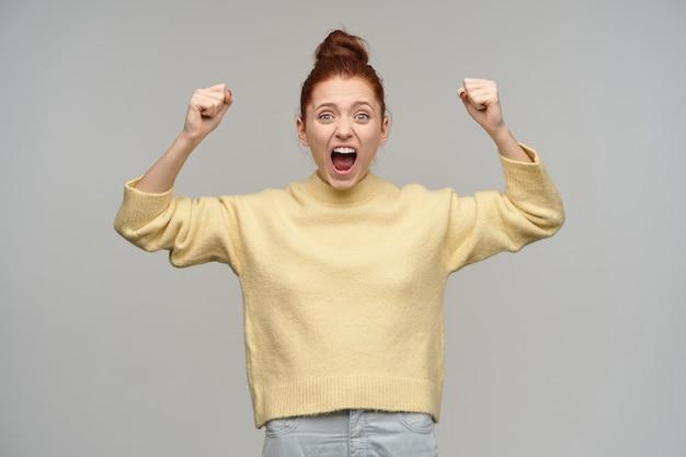 Portret van opgewonden, roodharig meisje met haar verzameld in een knot. pastelkleurige gele trui en spijkerbroek aan. heft vuisten op en schreeuwt. vier de overwinning. geïsoleerd over grijze muur