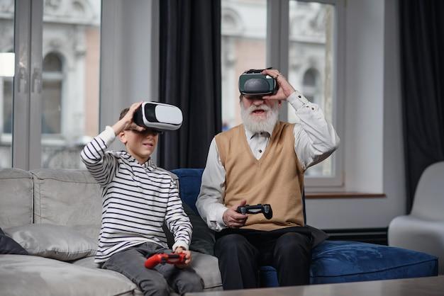 Portret van opgewonden senior man met vr-bril zittend op de bank thuis met lachende kleinzoon naast hem