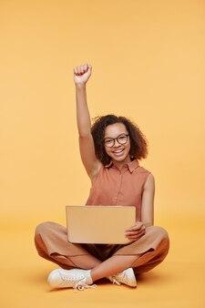 Portret van opgewonden studentenmeisje zittend met laptop op knieën en arm omhoog tegen gele achtergrond