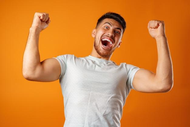 Portret van opgewonden, succesvolle man handen omhoog close-up