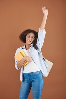 Portret van opgewonden tienermeisje met studentenboek dat met de hand zwaait?