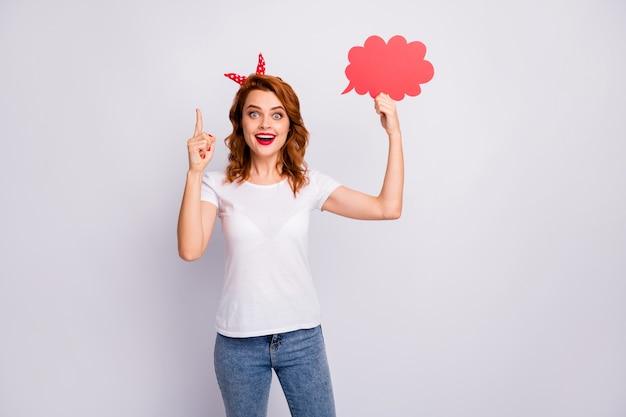 Portret van opgewonden verbaasd meisje houdt rode papercard sppech-bel denk gedachten beslissen beslissingen kies keuze oplossing draag stijlvolle outfit geïsoleerd over witte kleur muur