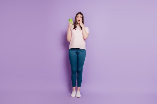 Portret van opgewonden verbaasde meisjesachtige dame houdt mobiele telefoon palm wang open mond op violette achtergrond