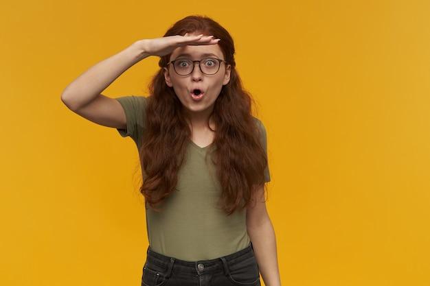 Portret van opgewonden, verraste dame met lang gemberhaar. groen t-shirt en brillen dragen. staar in de verte met de handpalm voor haar ogen. geïsoleerd over oranje muur