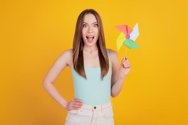 Portret van opgewonden verraste schattige dame houdt speelgoedpropeller omg reactie open mond op gele achtergrond