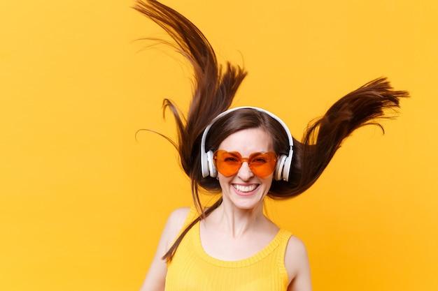 Portret van opgewonden vrolijk gelach grappige komische vrouw in oranje bril in koptelefoon met fladderende haren geïsoleerd op gele achtergrond. mensen oprechte emoties, lifestyle concept. advertentiegebied
